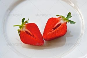Cut strawberry on a plate by version-four
