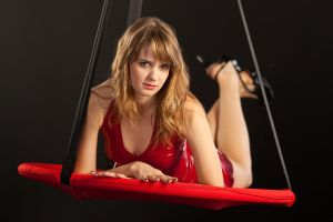 Dasha in red latex dress laying in a teeter by pnlabs