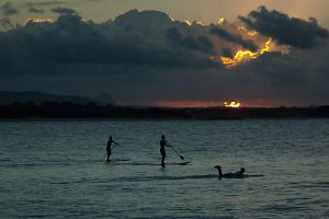 Paddleboarders at sunset by wildplaces